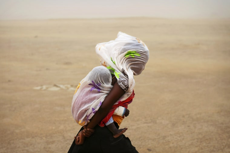 Image: A woman carrying her baby and wrapped with a shawl walks through a sandstorm in Timbuktu