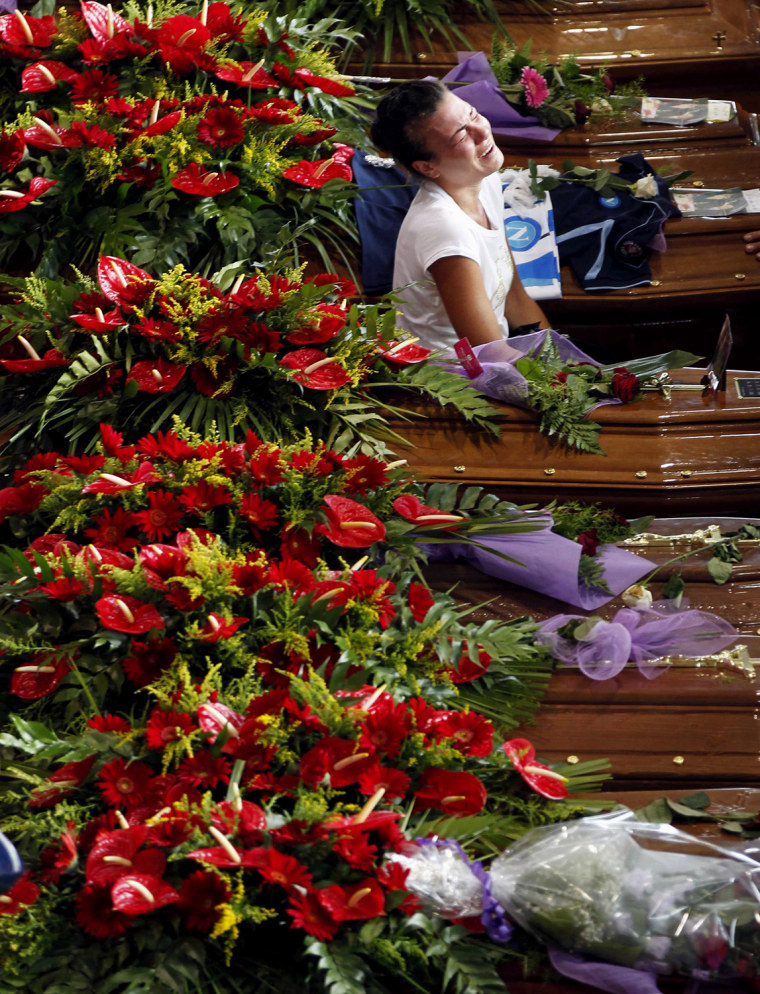 Image: A woman cries next to the coffins of victims of a coach crash during the funeral service at the Monteruscello Palasport near Pozzuoli