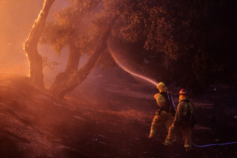 Image: Firefighters spray water near a burning house in the Twin Pines Road area at the Silver Fire near Banning, California.