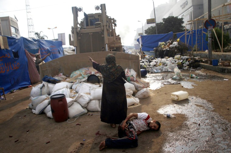 Image: A woman tries to stop a military bulldozer from hurting a wounded youth during clashes that broke out as Egyptian security forces moved in to disperse supporters of deposed president Mohammed Morsi.