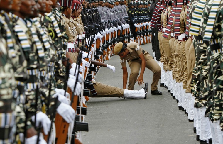 Image: An Indian policewoman helps her comrade who fainted during the full-dress rehearsal for India's Independence Day celebrations in Chennai