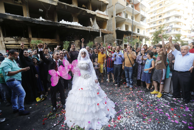 Image: People cheer as a Lebanese bride and groom pose for pictures