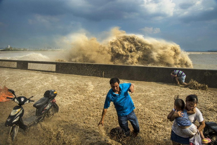 Image: Visitors run away as waves from a tidal bore surge past a barrier on the banks of Qiantang River, in Hangzhou
