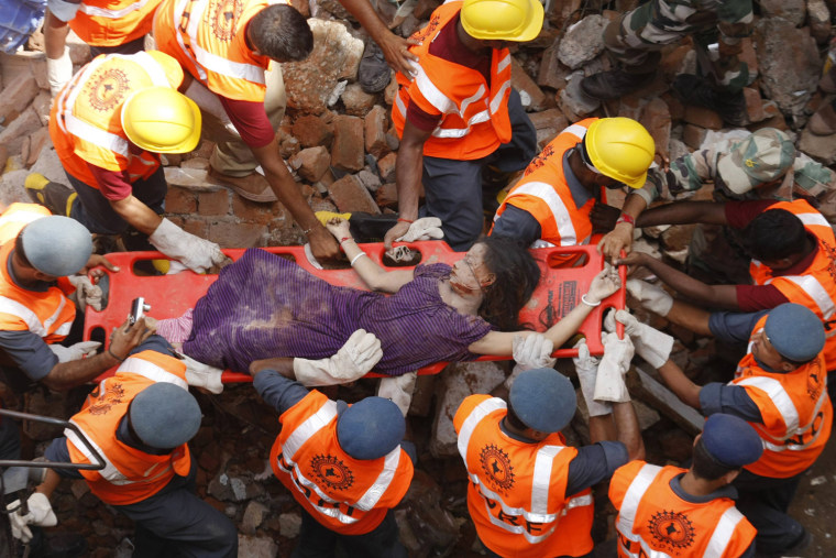 Image: Rescue workers use a stretcher to carry a victim across the rubble after the collapse of two residential buildings in Vadodra city