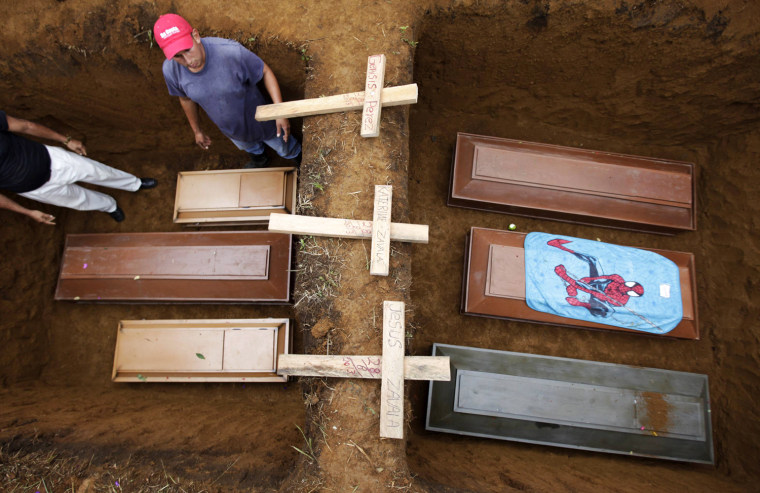 Image: Men stand next to coffins during the funeral for six children who died in a landslide in La Chicharronera