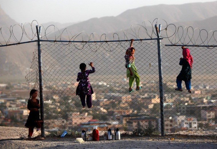 Image: Afghan children climb onto a fence while playing as they sell tea in Kabul