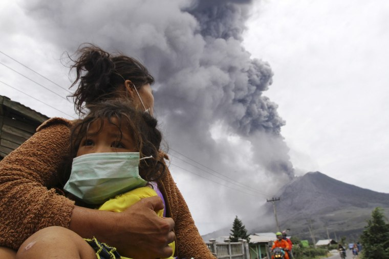 Image: A mother holds her child as Mount Sinabung spews ash and hot lava during an eruption in Perteguhan village