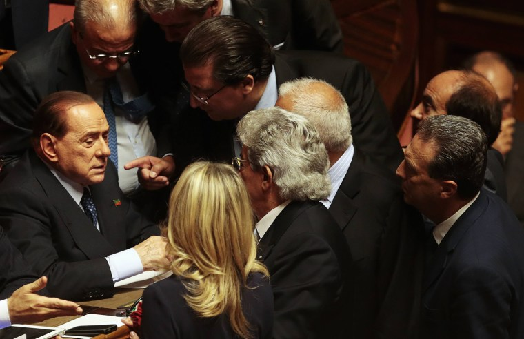 Image: Italian center-right leader Berlusconi talks with senators at the Senate after PM Letta's asking for possible call for confidence vote immediately in Rome
