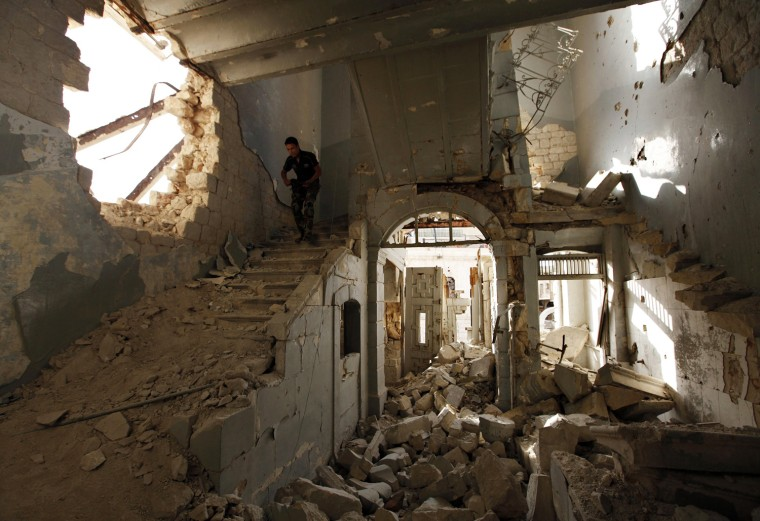 Image: A Free Syrian Army fighter carries his weapon as he walks down the stairs of the damaged former Immigration and Passport building in Aleppo