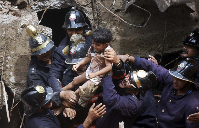 Image: Rescue workers carry a girl who was rescued from the rubble at the site of a collapsed residential building in Mumbai