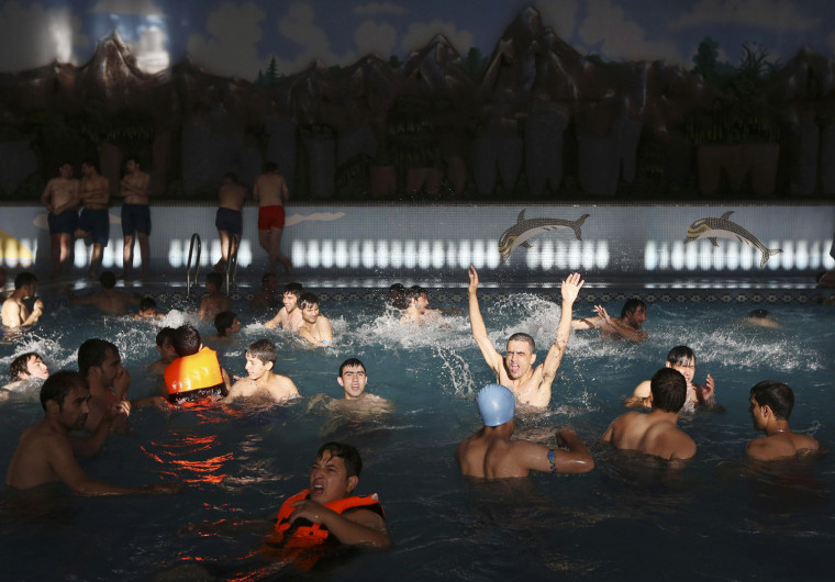 Image: People swim and play around at a public swimming pool in Kabul