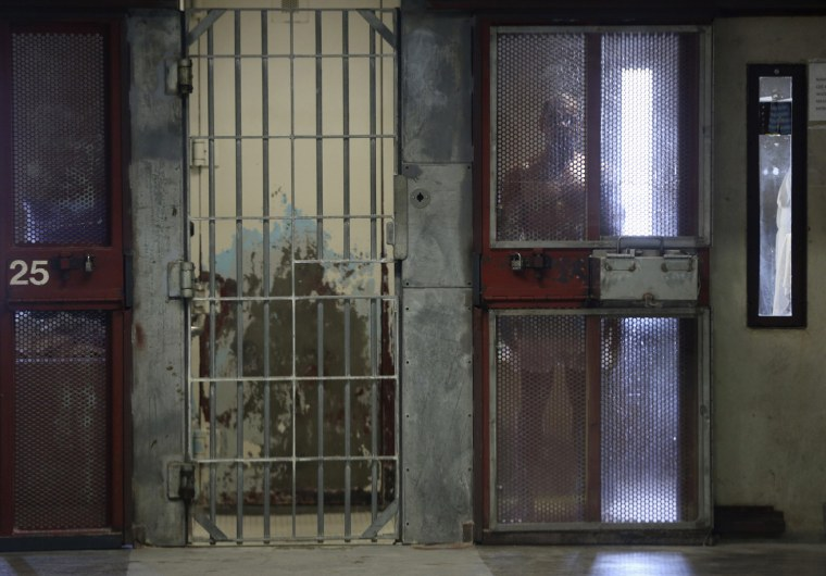 Image: An inmate looks out from his cell in the Secure Housing Unit at Corcoran State Prison in California