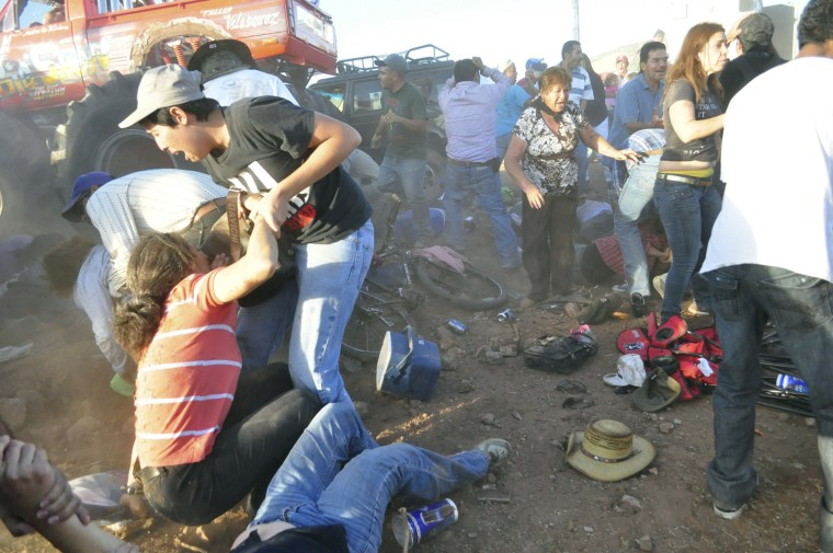 Image: Spectators react after a monster truck rammed the stand where they were watching a monster truck rally show at El Rejon park, Chihuahua
