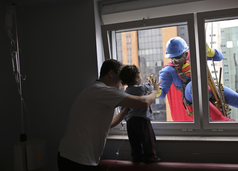Image: Men dressed as cartoon characters meet with children's hospital patients in Sao Paulo