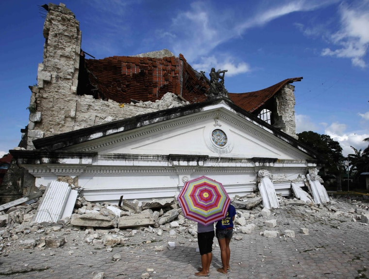 Image: Residents look at collapsed Holy Trinity parish church at Loay, Bohol after an earthquake struck central Philippines
