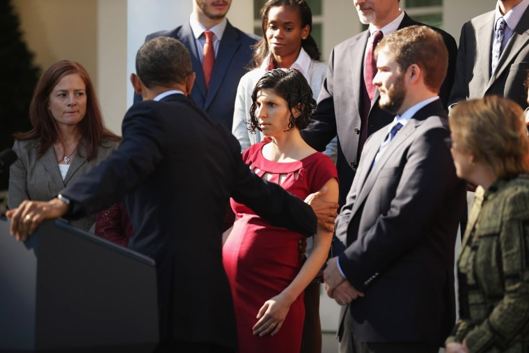 Image: President Barack Obama assists a woman who became dizzy during his remarks