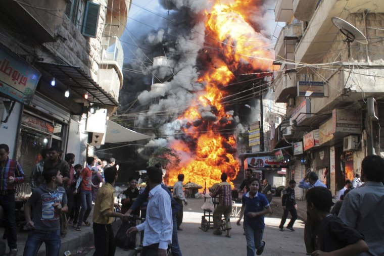 Image: Residents look at a a fire at a gasoline and oil shop in Bustan Al-Qasr