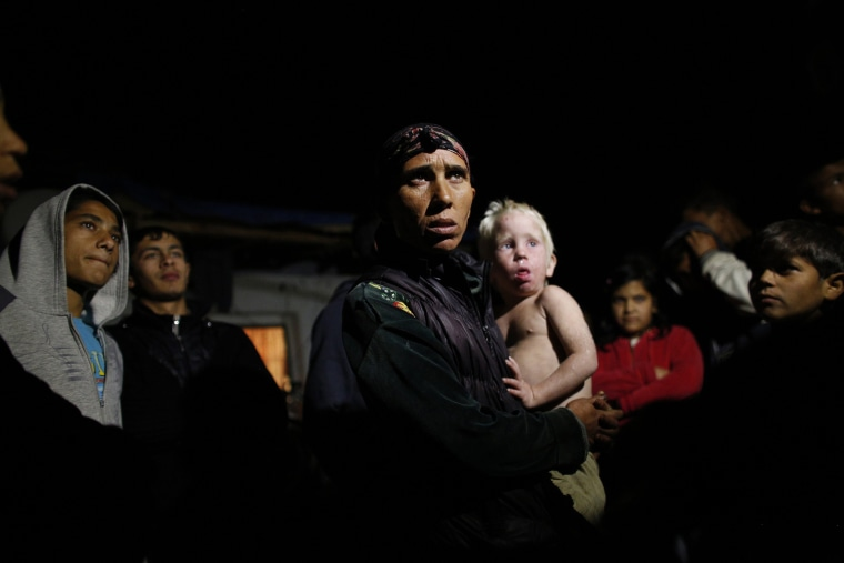 Image: Bulgarian Roma Sashka Ruseva, 38, holds her son Atanas, 2, as she speaks to media outside her house in the town of Nikolaevo