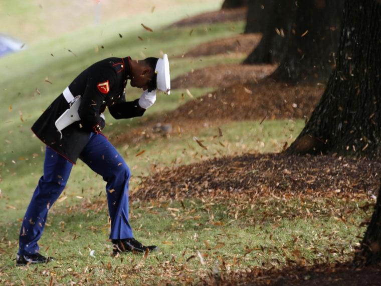 Image: A U.S. Marine holds his hat as U.S. President Barack Obama lands in Bethesda, Maryland