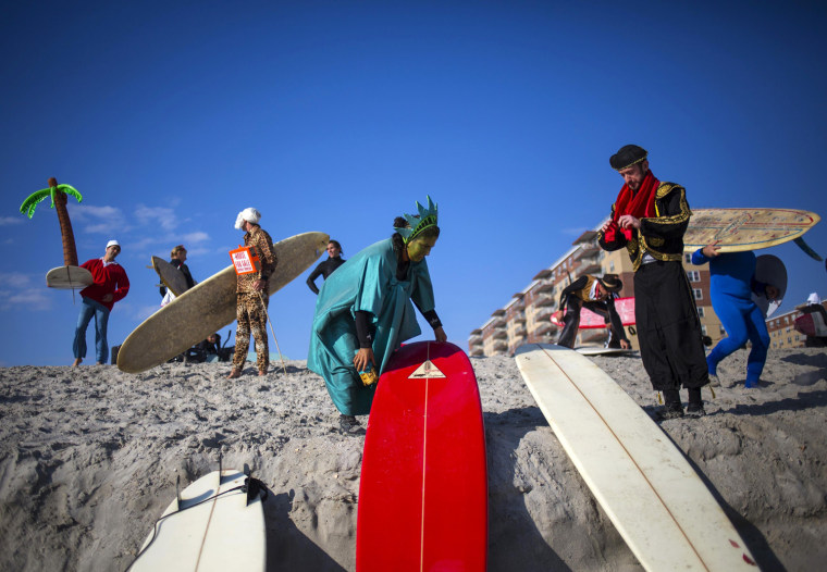 Image: Participants prepare before the third annual Rockaway Halloween surf competition at Rockaway Beach in the Queens borough of New York