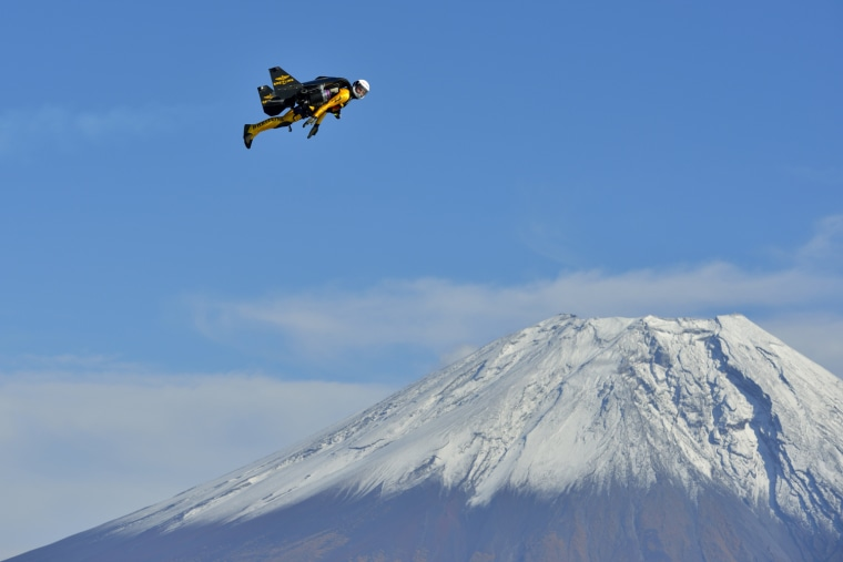 Image: Yves Rossy, known as the Jetman, flies over the snow-capped peak of Mount Fuji, Japan