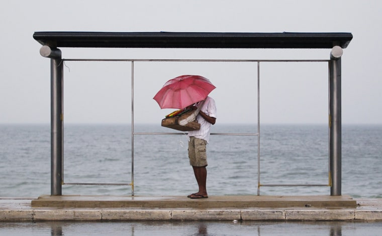 Image: A vendor holds up an umbrella as he seeks shelter from the heavy rain under a bus stand near the Galle Face beach in Colombo