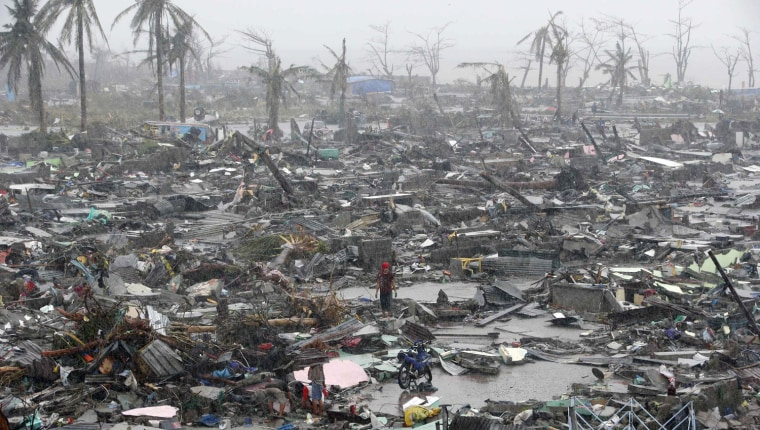 Image: Survivors stand among debris and ruins of houses destroyed after Super Typhoon Haiyan battered Tacloban city in central Philippines