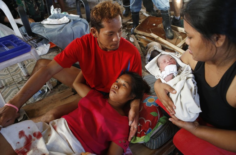 Image: A relative holds newly born baby Beatriz as her mother recuperates at a makeshift birthing clinic in Tacloban city in central Philippines