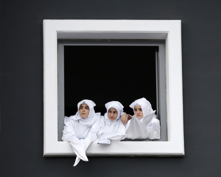 Image: Turkish Shi'ite girls watch a re-enactment of the battle of Kerbala on a huge screen during an Ashura procession in Istanbul