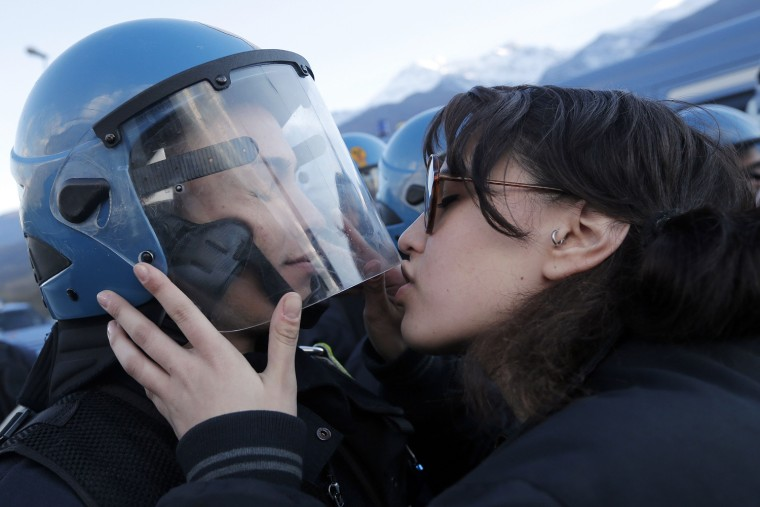Image: A demonstrator kisses a riot police officer