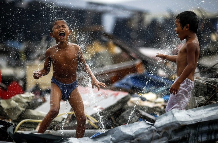 Image: Children shower near the debris of an area destroyed by Typhoon Haiyan in Tacloban City