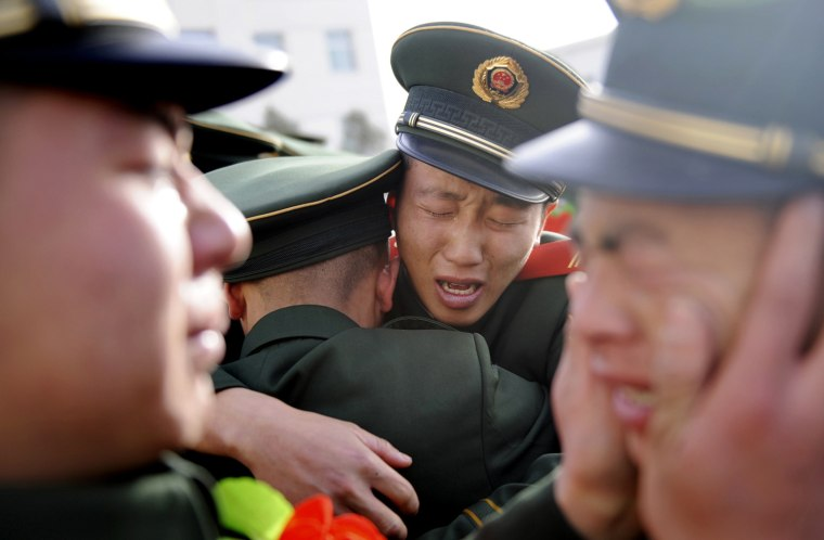 Image: Chinese paramilitary policemen cry as they see off veterans during a farewell ceremony in Taiyuan