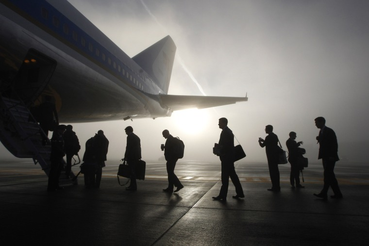 Image: Travelling White House staff and press board the rear steps of Air Force One on a foggy morning in Seattle