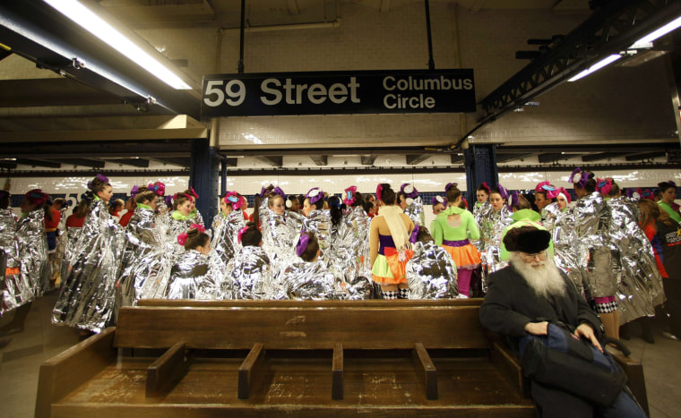 Image: Performers in the 87th Macy's Thanksgiving Day Parade wait for a subway in New York