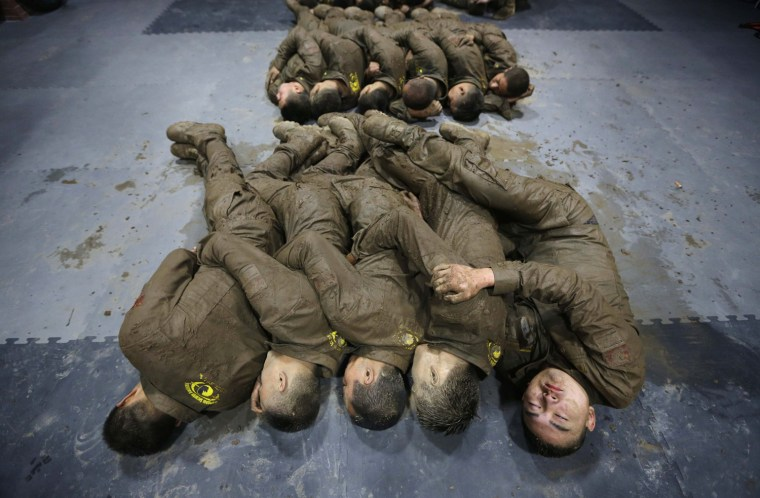 Image: Students hold each other for warmth as they sleep during a break in between high intensity training at Tianjiao Special Guard/Security Consultant camp on the outskirts of Beijing