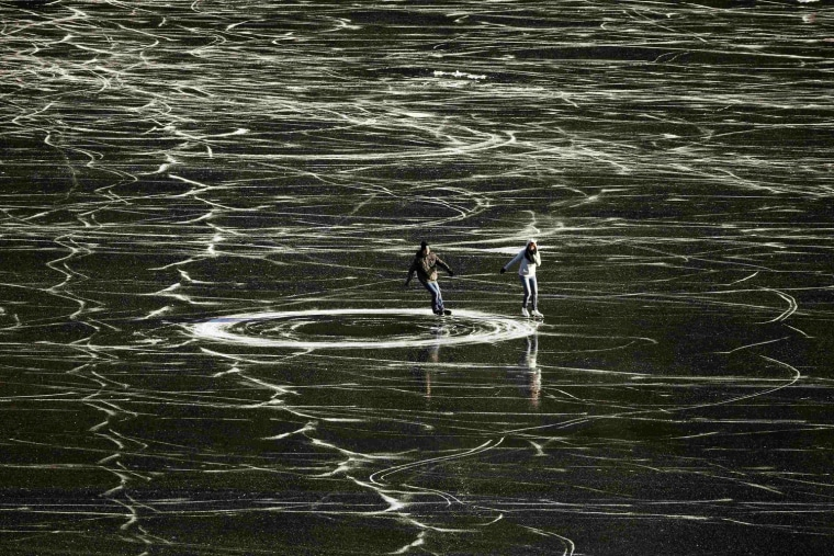 Image: A couple skates on the frozen waters of Lake St. Moritz