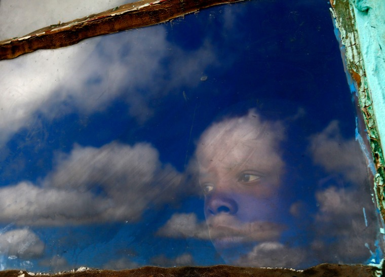 Image: A local boy, Anda, looks out from his hut's window at the burial ground of late former South African President Nelson Mandela ahead of his funeral in Qunu