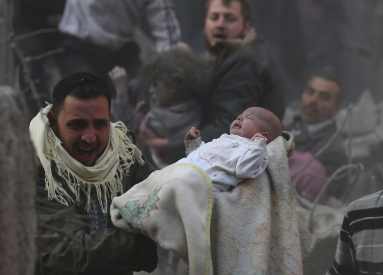 Image: A man carries a baby who survived what activists say was an airstrike by forces loyal to Syrian President Bashar al-Assad in the Duma neighbourhood of Damascus