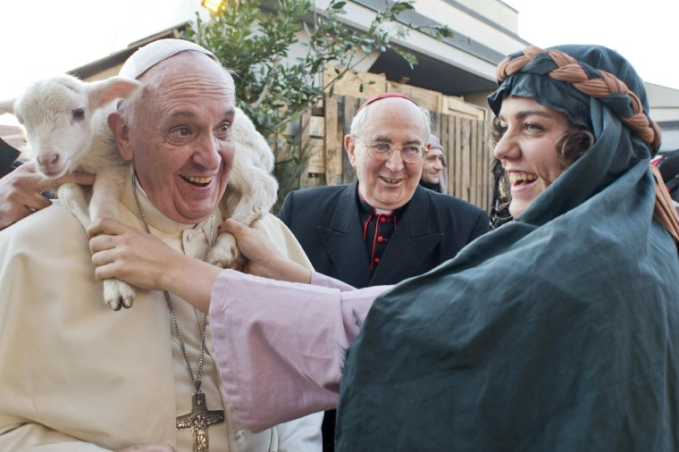 Image: A woman dressed as a character from the nativity scene puts a lamb around the neck of Pope Francis as he arrives to visit the Church of St Alfonso Maria dei Liguori in the outskirts of Rome