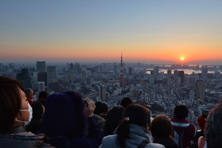 Image:  People watch the sun rise on New Year's Day in Tokyo.