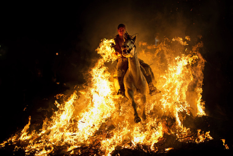 Image: A man rides a horse through a bonfire as part of a ritual in honor of Saint Anthony.