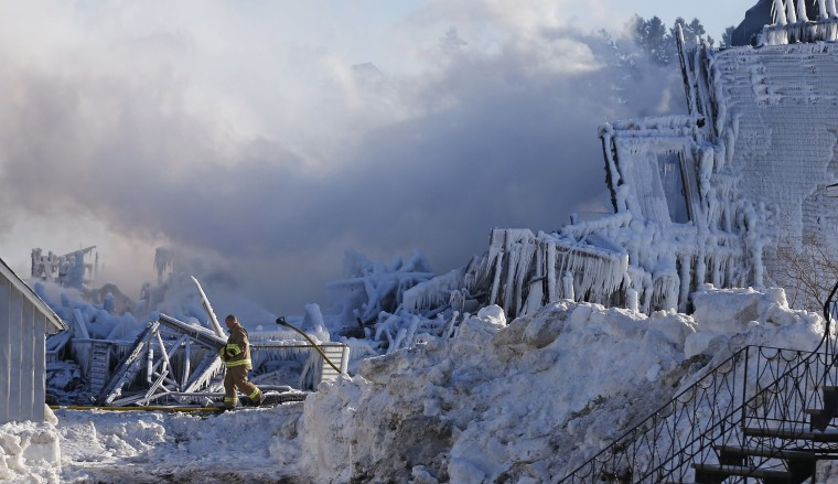 Image: A firefighter walks past the Residence du Havre after a fire in L'Isle Verte, Quebec