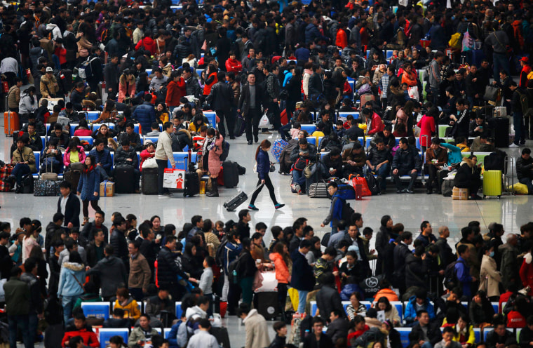Image: People wait for their trains at Hongqiao train station in Shanghai