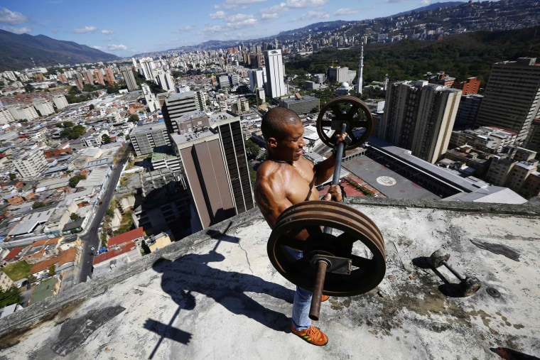 """Image: Rivas lifts weights on a balcony on the 28th floor of the """"Tower of David"""" skyscraper in Caracas"""