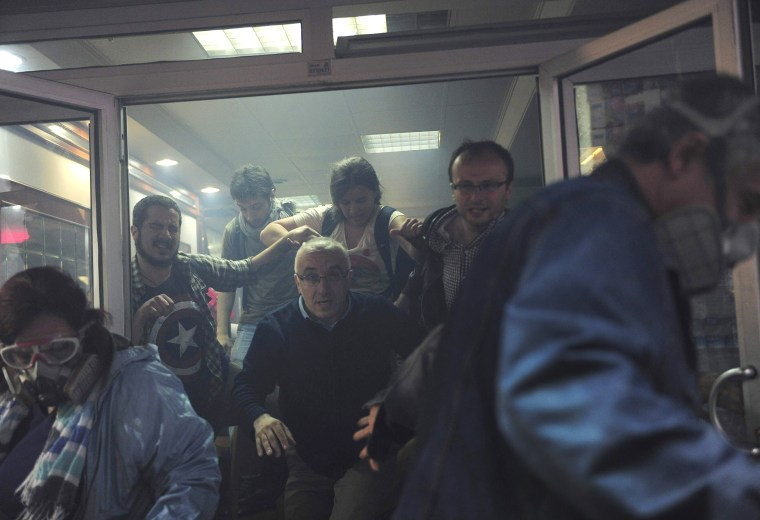 Image: People try to escape from a cafe, after tear gas fired by riot police outside to disperse protesters seeped in, at central Istanbul