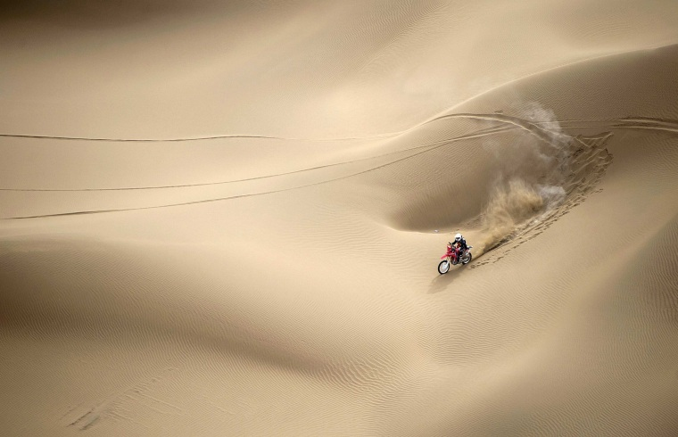 Image: Wang Yirong of Hebei province rides his motorcycle in a desert during the China Taklimakan Rally and CCR Xinjiang Station, in Shanshan