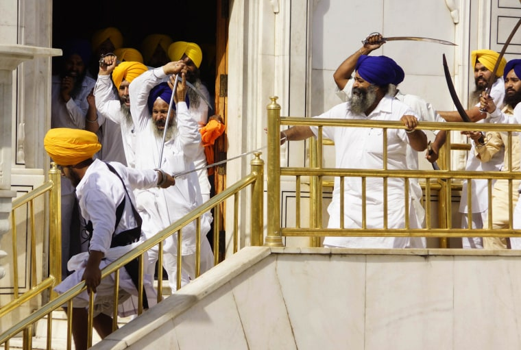 Image: Members of a hardline Sikh group clash with guards of the Sikhs' holiest shrine, the Golden Temple, in Amritsar, India