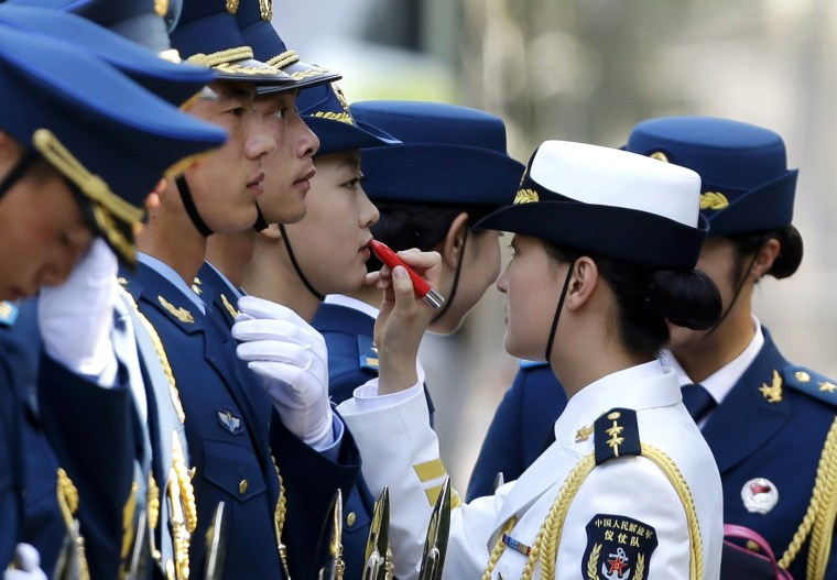 Image: Female honour guard has lipstick applied as they prepare for an official welcoming ceremony for Italy's PM Renzi outside the Great Hall of the People in Beijing