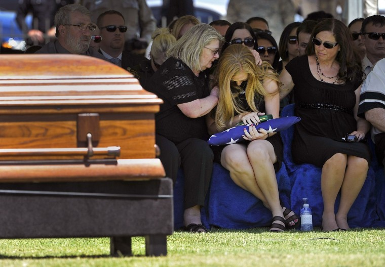 Image: Andrea Soldo is consoled by family members after receiving U.S. national flag that was draped over casket of her husband, Las Vegas police officer Igor Soldo, during funeral services for Soldo at Palm Northwest Mortuary & Cemetery in Las Vegas