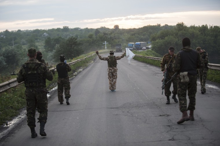 Image: Pro-Russian fighters wave a white flag to start a handover of the bodies of Ukrainian troops killed